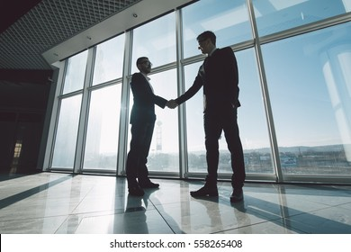 Two young businessmen are shaking hands with each other standing against panoramic windows.