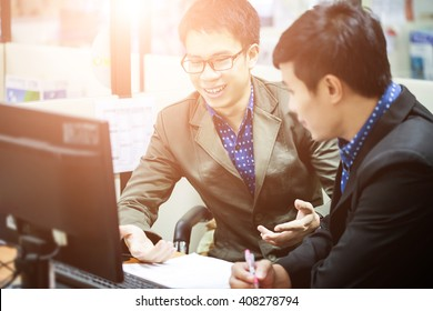 two young businessmen using computer at meeting ( soft focus with sunrise morning)