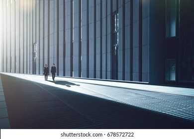 Two young businessmen walking in the streets of facade with metal and stripes design construction in modern building .