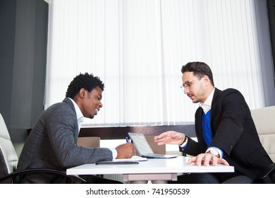 Two young businessmen, white desk, job interview, teamwork. Two successful male entrepreneurs at office work together