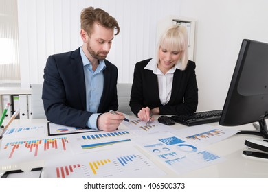 Two Young Businesspeople Analyzing Financial Graphs In Office