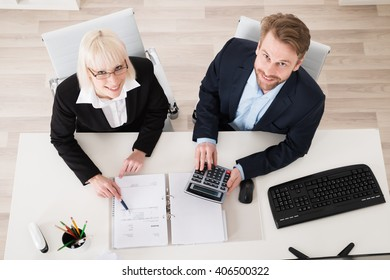 Two Young Businesspeople Calculating Tax In Office