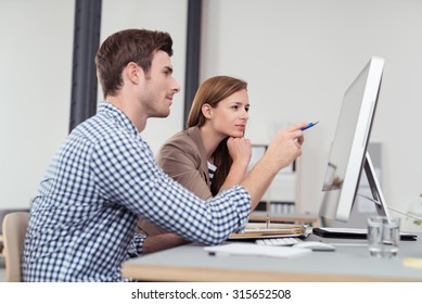 Two Young Businesspeople Sitting at the Table and Looking at the Figures on the Computer Screen