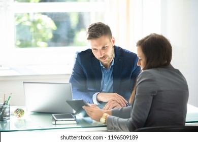 Two Young Businesspeople Using Digital Tablet At Workplace