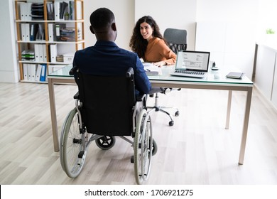 Two Young Businesspeople Working On Laptop At Workplace