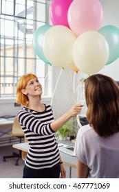 Two young businesswomen celebrating in the office with a large bunch of colorful party balloons smiling happily as they watch them float in the air