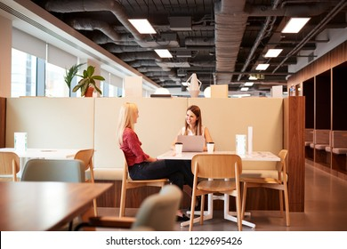 Two Young Businesswomen Having Informal Interview In Cafeteria Area At Graduate Recruitment Assessment Day