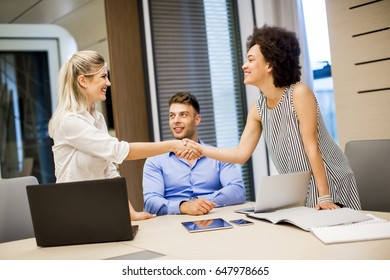 Two young businesswomen shaking hands after a job well done in modern office