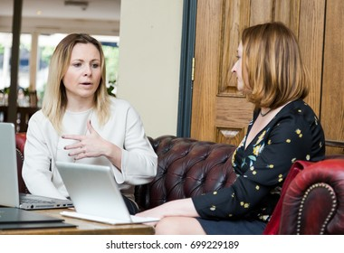 Two young businesswomen sitting on leather sofa having informal business meeting. Low angle perspective with selective focus on explicit face. Horizontal crop