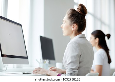 Two young businesswomen or students sitting in computer class in front of monitors