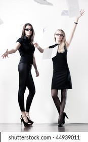 Two young businesswomen throwing out paper. On bright white wall background.