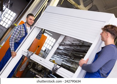 Two young careful workers inspecting windows with shutter at workshop