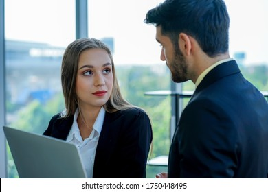 two young caucasian business womwan and colleage discuss the financial business plan from laptop comuter in the office