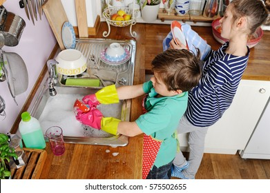 Two young caucasian children are doing the dishes in kitchen at home