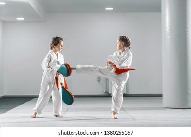 Two young Caucasian girls in doboks having taekwondo training at gym. One girl kicking while other one holding kick target.