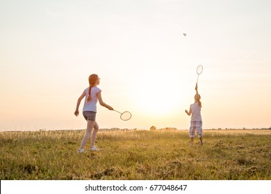 Two young caucasian kids playing badminton in the field at summer sunset