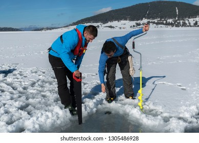 Two young Caucasian man looking at a hole on an ice on a frozen lake with saw and ice drill auger. Selective focus