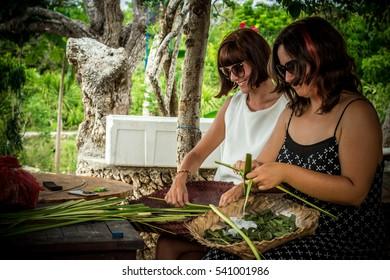 Two young caucasian pretty woman preparing balinese hindu offerings to Gods in wooden gazebo. Tropical island Bali, Indonesia.