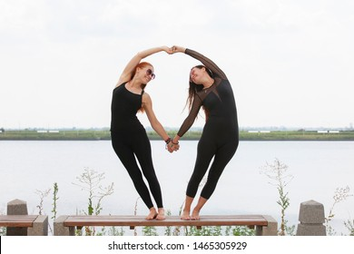 Two young Caucasian women yogi doing balance back stretch acro yoga pose. Women doing stretching workout in park outdoors at sunset. Healthy lifestyle modern activity. Portrait