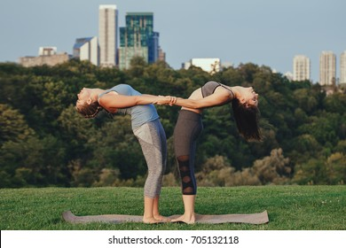 Two young Caucasian women yogi doing balance back stretch acro yoga pose. Women doing stretching workout in park outdoors at sunset. Healthy lifestyle modern activity