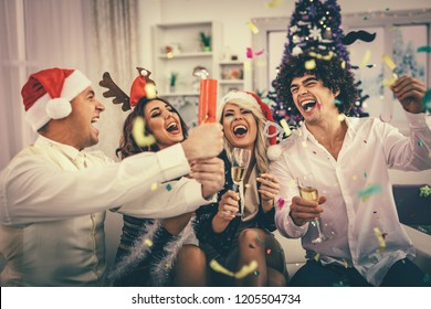 Two young cheerful couples celebrating Christmas with confetti at the home. They are having fun and toasting with champagne.