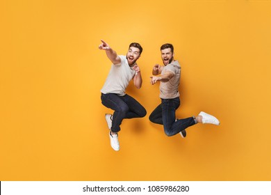 Two young cheerful men jumping together and pointing away isolated over yellow background