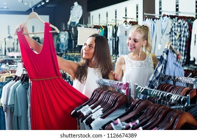 two young cheerful russian women picking new dress in fashion department
