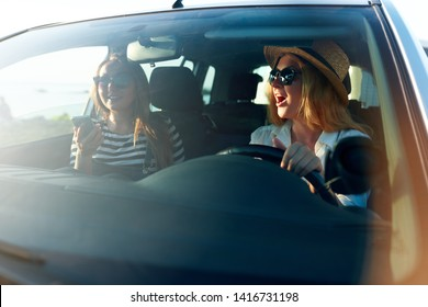 Two young cheerful smiling women in a car on vacation trip to the sea beach. Girl in glasses driving a vehicle from rental on holidays. Girlfriends enjoying summer arrived to ocean shore on holidays.