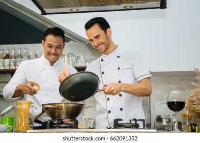 Two young chefs are preparing and cooking food at the kitchen of a restaurant