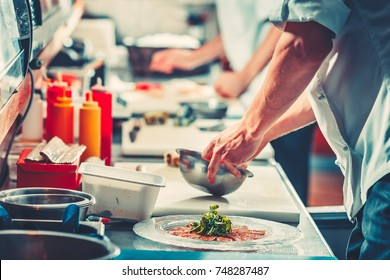 Two young chefs in white uniform preparing delicious fish meat snack salad, only hands close up. Interior of modern restaurant kitchen. Food concept. Vintage instagram Color filter toning