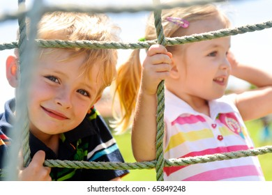 Two young children climbing the net in the playground