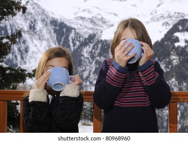 Two young children drinking from large cups in a ski resort