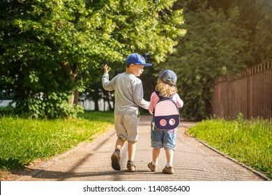 Two young children friends boy and girl hold hands and walk along road in the summer green park on sunny afternoon. Child friendship. Children are walking in the park.