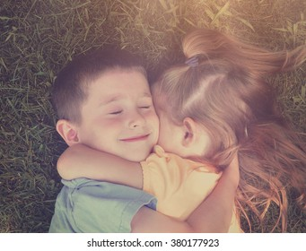 Two young children are hugging on the ground with grass in the background and sunshine for a love or friendship concept.