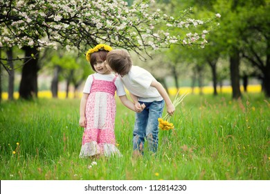 Two young children kissing in flowery meadow of long grass, girl wearing daisy flower crown.