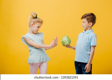 two young children, Little boy proposes young little cabbage, healthy food concept, in blue T-shirt, isolated yellow background, copy space