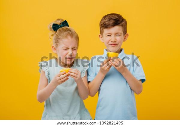 zwei kleine Kinder, kleines Mädchen und kleiner Junge schmecken sauer Zitrone emotional, mit wunden, gesichtsempirischen Emotionen negativ, in blauem T-Shirt, einzeln gelber Hintergrund, Kopienraum