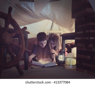 Two young children are reading a book together with sparkles in a tent fort at home for a story time or learning concept.