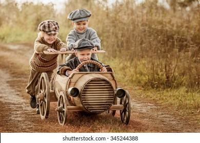 Two young children ride in the third race car from wooden barrels on a rural road autumn evening