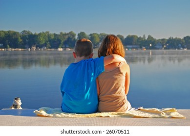 two young children show their affection in the early morning at the lake