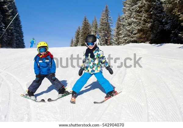 Two young children, siblings brothers, skiing in Austrian mountains on a sunny day, wintertime, enjoying sports
