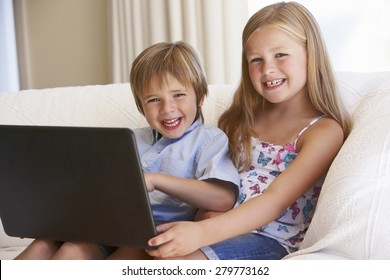 Two Young Children Using Laptop At Home