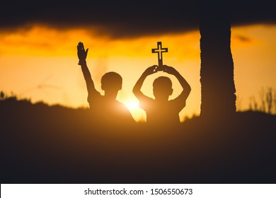 Two young christians worshiping God ,christian silhouette  concept.