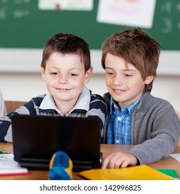 Two young classmates studying with laptop at the classroom