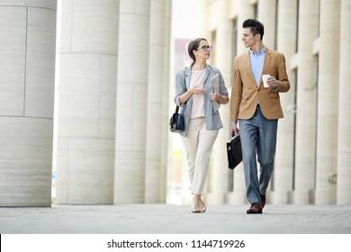 Two young colleagues in formalwear having talk while going back home from work
