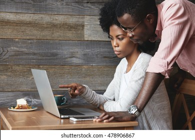 Two young colleagues using laptop. Double exposure of African boss dressed in formal wear, watching his female assistant presenting her report on computer, who is pointing her finger at screen