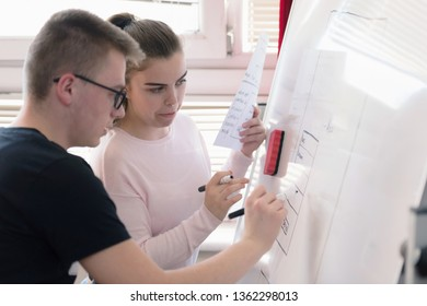 Two young college students writing on the chalkboard/blackboard during a  class. Resolving math problem or presenting their idea for resolution.