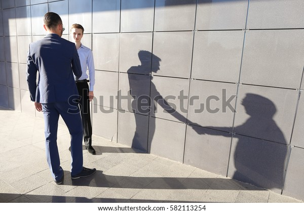 Two young confident man businessman met and greet each other with handshake near modern business center outdoors. Guy with glasses standing with his back to camera and dressed in classic blue suit