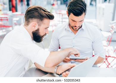 Two young contemporary businessmen working outdoor sitting in a bar using a smart phone and a notebook, both smiling - technology, business, work concept - copy space on left