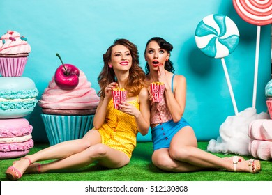 Two young cool lady on turquoise background, sitting on the grass and eating popcorn, laughing, best friends, crazy emotions, Huge candy, lollipops, cotton candy, Cake, fashionable Pin up girl